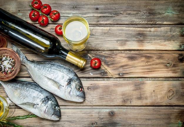 Roher seefisch mit gewürzen und weißwein. auf einem hölzernen hintergrund.