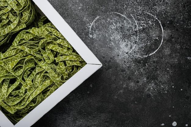 Roher spinat tagliatelle green pasta pack set, auf schwarzem, dunklem steintischhintergrund, draufsicht flach, mit kopierraum für text