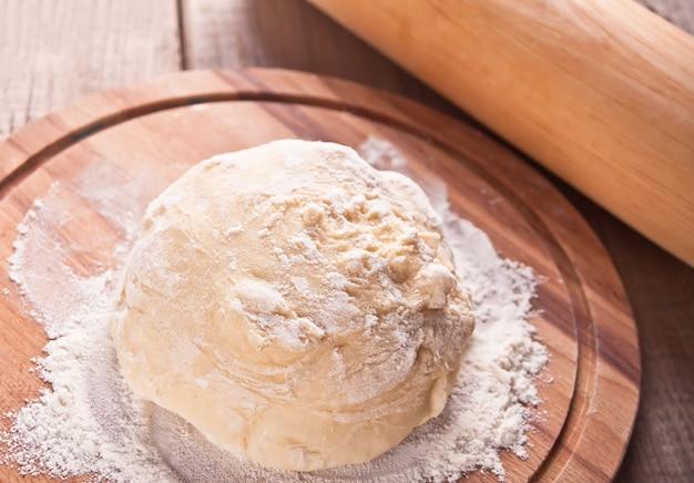 Roher teig für das pizza- oder brotbacken auf hölzernem schneidebrett auf schwarzem