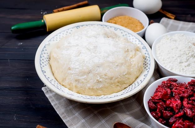 Roher teig in einer schüssel und zutaten für die herstellung von kuchen