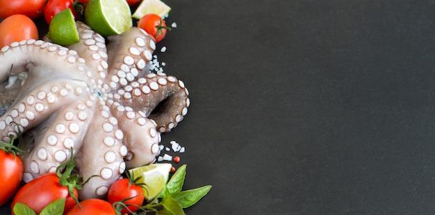 Roher tintenfisch mit limette, tomaten und basilikum schließen oben auf einem dunklen tisch mit kopienraum