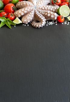 Roher tintenfisch mit limette, tomaten und basilikum über dunklem tisch schließen oben mit kopienraum