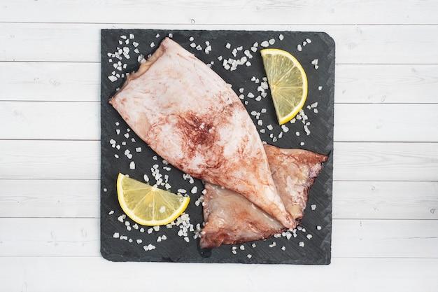 Roher tintenfischkadaver mit gewürzen und grobem salz auf einem schwarzen schieferbrett. kopienraum ansicht von oben.