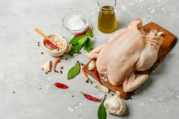Roher truthahn oder rohes huhn mit gewürzen lorbeerblatt, knoblauch, salz, chili und olivenöl. rezept für ein familienessen. ketodiätnahrung.
