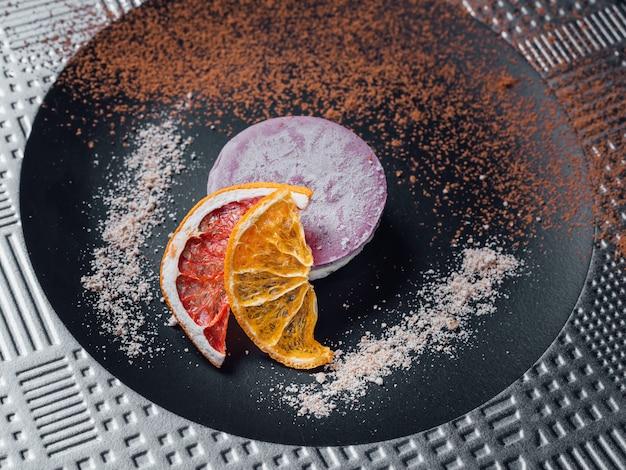 Roher veganer kuchen aus getrockneten früchten, nüssen und cremiger cashewzusammensetzung, kokosnussbutter, johannisbrot. auf der platte, isoliert auf schwarzem hintergrund, nahaufnahme