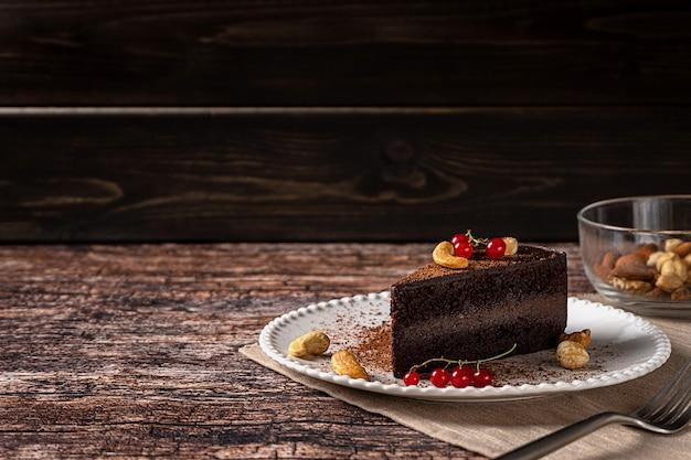 Roher veganer schokoladen-cashew-kuchen auf dunklem vintage-hintergrund