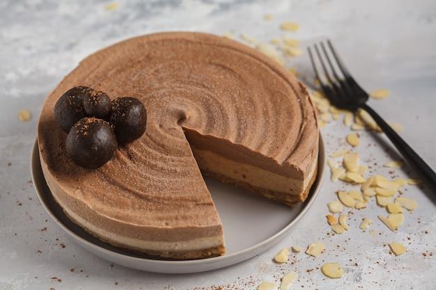 Roher veganer schokoladen-karamell-käsekuchen mit rohen kugeln. gesundes veganes dessertlebensmittelkonzept.