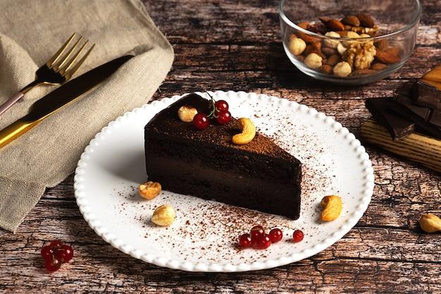 Roher veganer schokoladenkuchen auf dunklem vintage-hintergrund