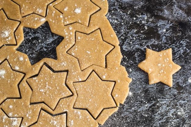 Roher weihnachtsselbst gemachter lebkuchenteig rollte heraus auf dunkler tabelle