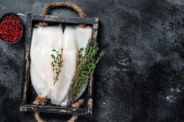 Roher weißer tintenfisch oder calamari in einem holztablett mit kräutern