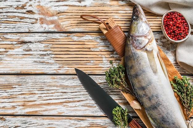 Roher zander, zanderfisch auf einem schneidebrett. frischer fisch. weißer hintergrund. draufsicht. speicherplatz kopieren.