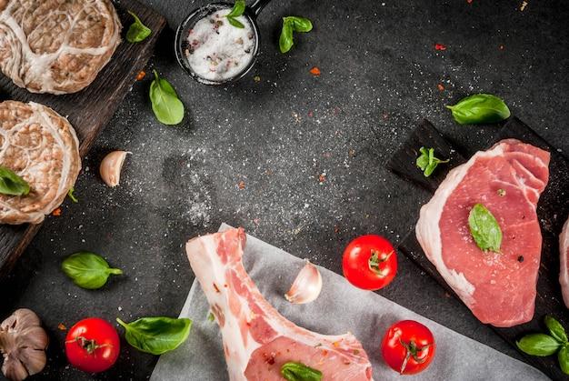 Rohes bio-fleisch. auswahl verschiedener roter fleischsorten: schweineschnitzel mit knochen, schweinesteaks und hühnerschnitzel in schweinefettgitter. mit zutaten zum kochen, graue stein tischplatte anzeigen