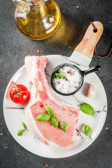 Rohes bio-fleisch. essen kochen. schweinefleisch auf knochen. schnitzel zum braten grillen. mit gewürzen und bestandteilbasilikum knoblauch, auf draufsicht des weißen marmorplattenschneidebretts der schwarzen tabelle