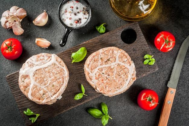 Rohes bio-fleisch. hühnerschnitzel für burger mit schweinefleischgitter zum grillen oder braten. mit gewürzen basilikum, tomaten, auf einer grauen steintabelle auf einem hölzernen brett des ausschnitts. ansicht von oben
