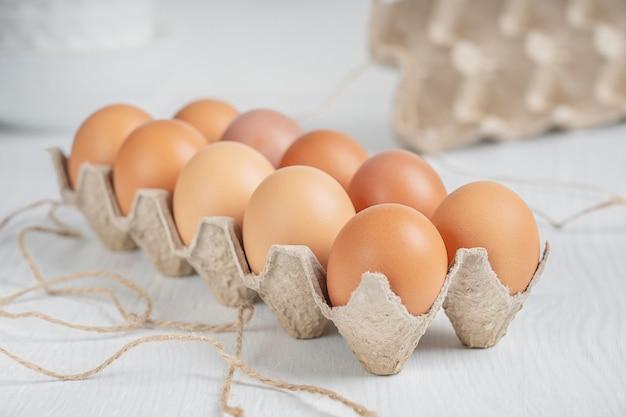 Rohes braunes dutzend frischer hühnereier in geöffnetem recyclingpapierkasten auf weißem holztisch in der küche