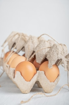 Rohes braunes dutzend hühnereier im halb geschlossenen weißen holztisch des recyclingpapierbehälters