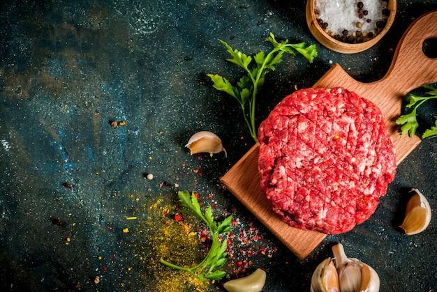 Rohes burgerkotelett mit salz, pfeffer, öl, kräutern und gewürzen