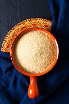 Rohes couscous des lebensmittelkonzepts in der orangefarbenen schüssel