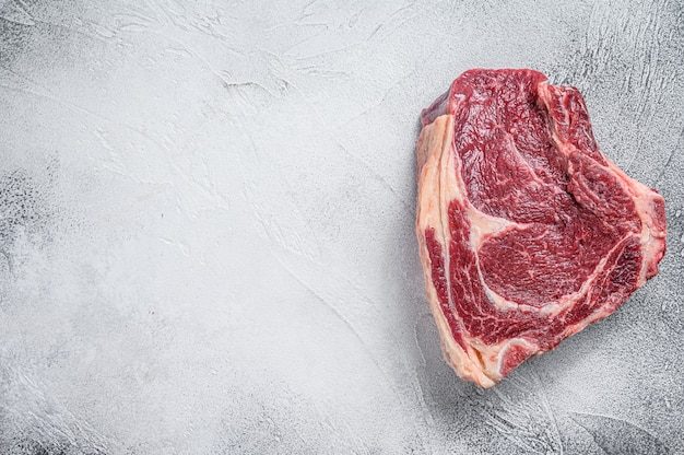 Rohes cowboy-steak oder rippenauge auf dem knochen auf marmorrindfleisch auf grauem tisch.