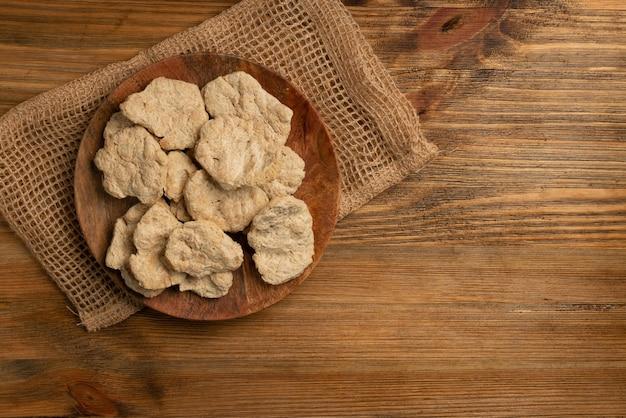 Rohes dehydriertes sojafleisch oder sojastücke auf holztischoberansicht. texturiertes pflanzliches protein, auch als texturiertes sojaprotein oder tsp bekannt