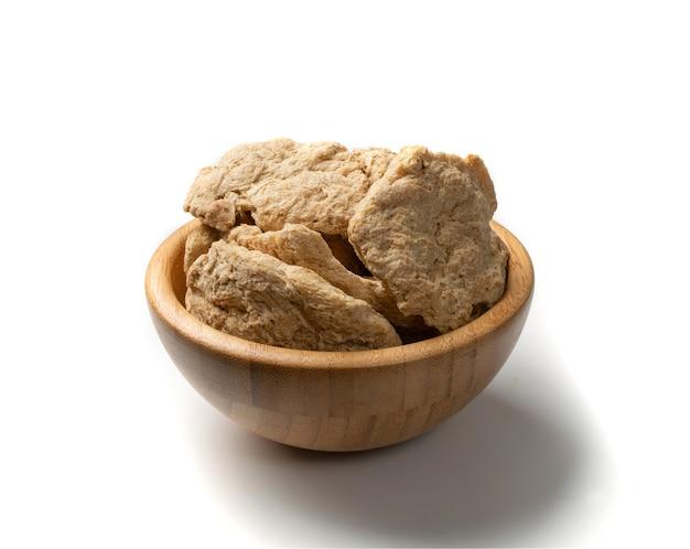 Rohes dehydriertes sojafleisch oder sojastücke in der holzschale isoliert. texturiertes pflanzliches protein, auch als texturiertes sojaprotein oder tsp bekannt