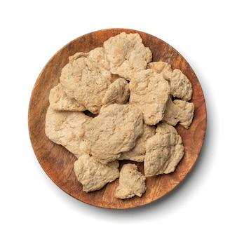 Rohes dehydriertes sojafleisch oder sojastücke isolierten draufsicht. texturiertes pflanzliches protein, auch als strukturiertes sojaprotein oder tsp auf runder holzplatte bekannt