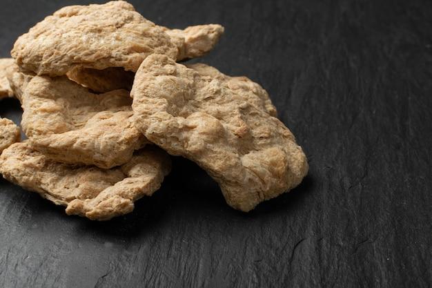 Rohes dehydriertes sojafleisch oder sojastücke schließen nah. texturiertes pflanzliches protein, auch als texturiertes sojaprotein oder tsp bekannt
