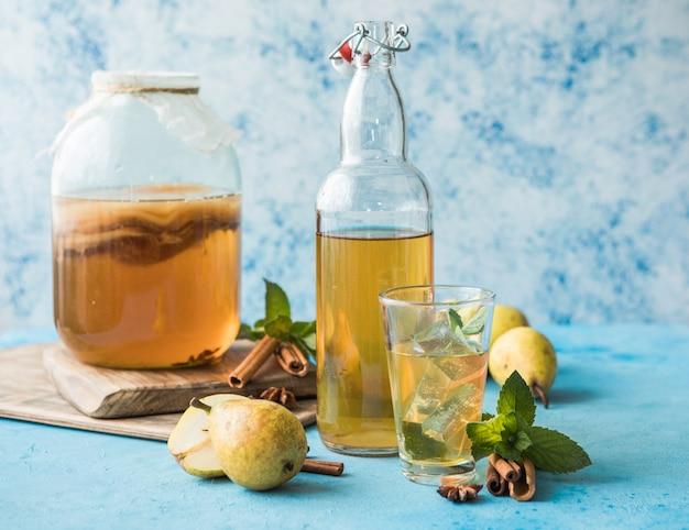 Rohes fermentiertes hausgemachtes alkoholisches oder nicht alkoholisches kombucha-superfood. eistee mit gesundem natürlichem probiotikum im glas mit minze auf blauem hintergrund