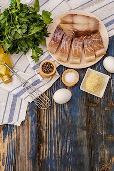 Rohes filet aus saithe und bratzutaten. frische scheiben auf einem teller, gewürze, eier, öl, semmelbrösel, petersilie