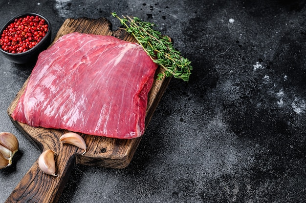 Rohes flanken- oder klappenrindfleischsteak auf einem hölzernen schneidebrett