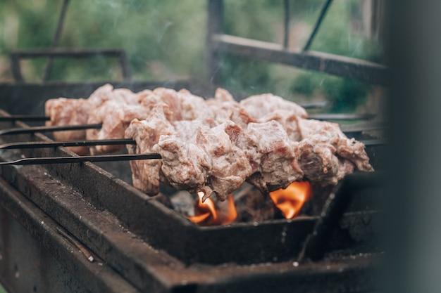 Rohes fleisch am spieß wird auf holzkohlegrill gegart, grillen im freien zubereitet