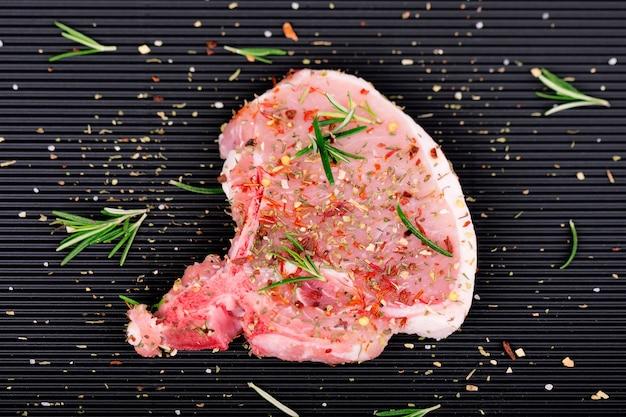 Rohes fleisch auf dunkel. rohes schweinefleischsteak mit kräutern und gewürzen