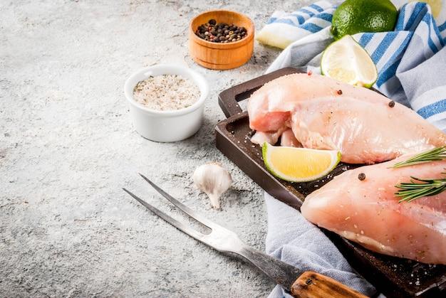 Rohes fleisch, bereit für grill- oder grillhähnchenbrustfilet, mit olivenöl, kräutern und gewürzen auf grauem steinhintergrund