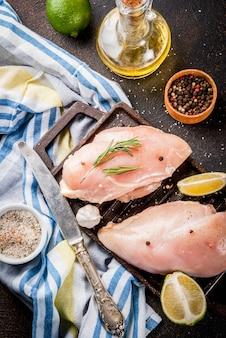 Rohes fleisch, bereit zur grill- oder grillhühnerbrustleiste, mit olivenöl, kräutern und gewürzen auf dunklem rostigem hintergrund, draufsicht des kopienraumes