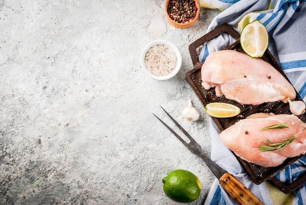 Rohes fleisch, bereit zur grill- oder grillhühnerbrustleiste, mit olivenöl, kräutern und gewürzen auf grauem steinhintergrund, draufsicht des kopienraumes