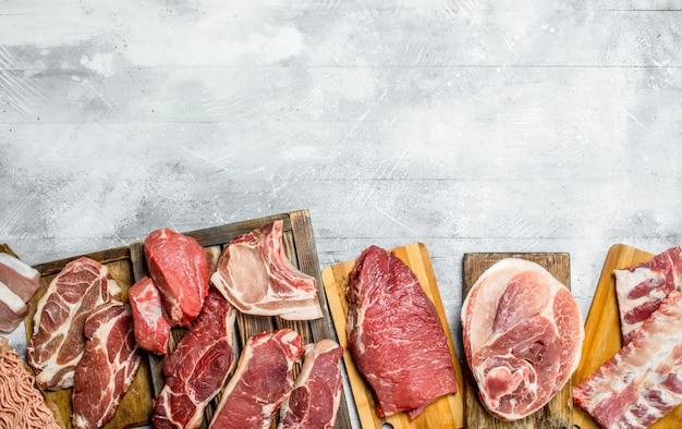 Rohes fleisch. die verschiedenen fleischsorten von schweinefleisch und rindfleisch. auf einem rustikalen hintergrund.