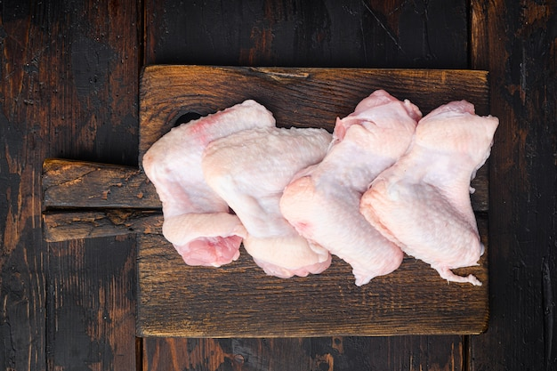 Rohes fleisch. hühnerflügel gesetzt, auf holzschneidebrett, auf altem dunklem holztisch tisch, draufsicht flach legen