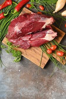 Rohes fleisch mit bestandteilen für das kochen auf braunem hölzernem schneidebrett.