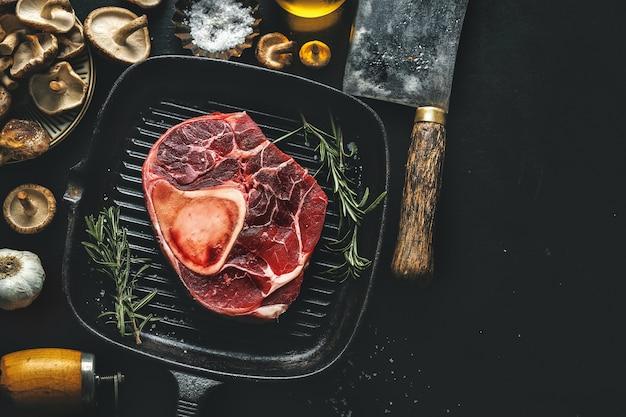 Rohes fleisch mit gemüse und gewürzen auf dunklem tisch. sicht von oben.