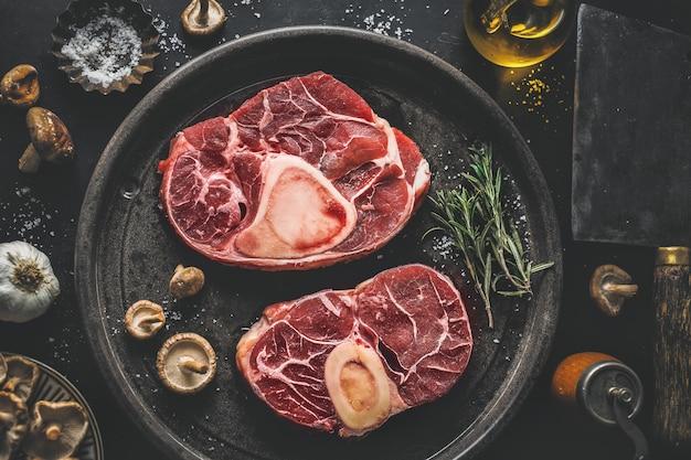 Rohes fleisch mit gemüse und gewürzen auf dunklem weinlesehintergrund. von oben betrachten.