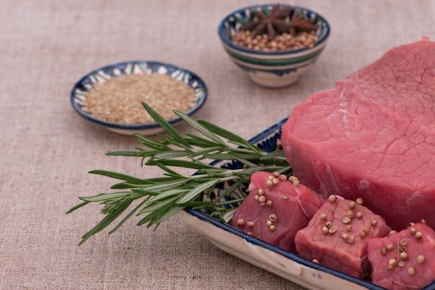 Rohes fleisch mit gewürzen und kräutern in einem quadratischen teller auf einem strukturierten gewebe