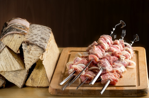 Rohes fleisch mit gewürzen und zwiebeln am spieß aufgereiht
