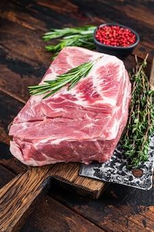 Rohes fleisch mit schweinehals für frische kotelettsteaks auf holzschneidebrett mit metzgerbeil. dunkles holz