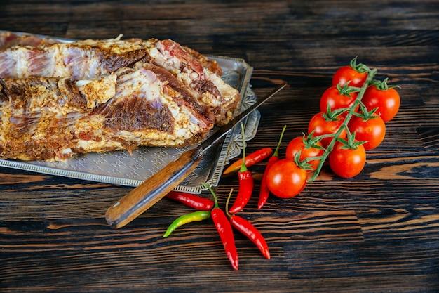 Rohes fleisch. rohes schweinefleisch auf gemüse und gewürzen eines schneidebretts auf schwarzem.