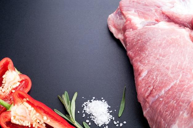 Rohes fleisch schweinefleisch mit gewürzen, kräutern und gemüse auf einem dunklen hintergrund