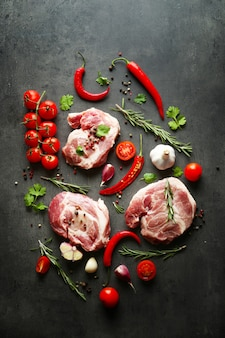 Rohes fleisch, tomaten und gewürze auf grau