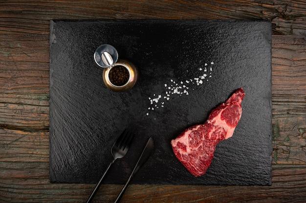 Rohes fleisch und gabelmesser und salz und pfeffer auf einer schwarzen steinplatte