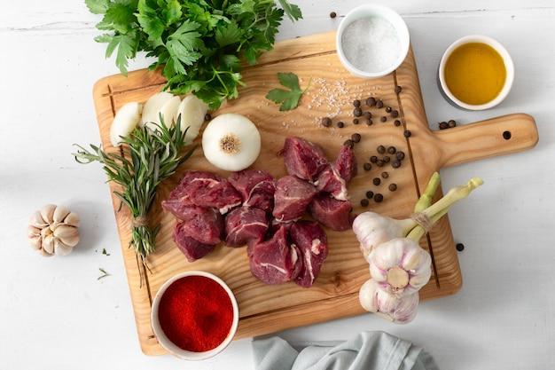 Rohes fleisch und gemüse auf draufsicht des weißen hölzernen brettes. rindfleisch kochen