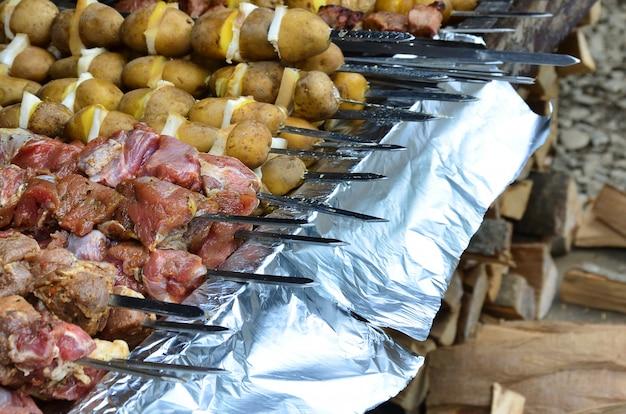Rohes fleisch und kartoffeln werden auf metallspieße gepflanzt. der prozess des kochens von schaschliks.