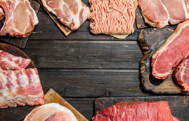 Rohes fleisch. verschiedene arten von schweine- und rindfleisch. auf einem hölzernen hintergrund.